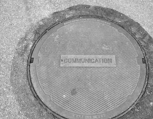 "Man hole cover reading ""communications"""